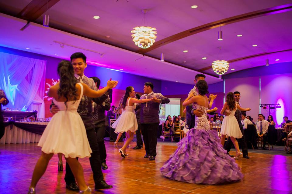 4 couples performing a dance in an event space, backlit by lights in hues of blue and purple.