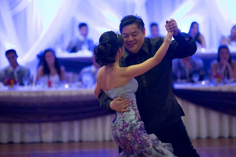 A touching image of a father-daughter dance with onlookers blurred in the background.
